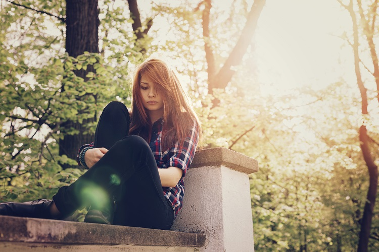 a depressed teen sits on a park bench