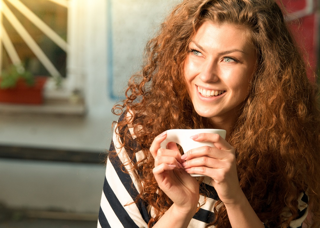 A smiling woman with curly brown hair holds a coffee mug