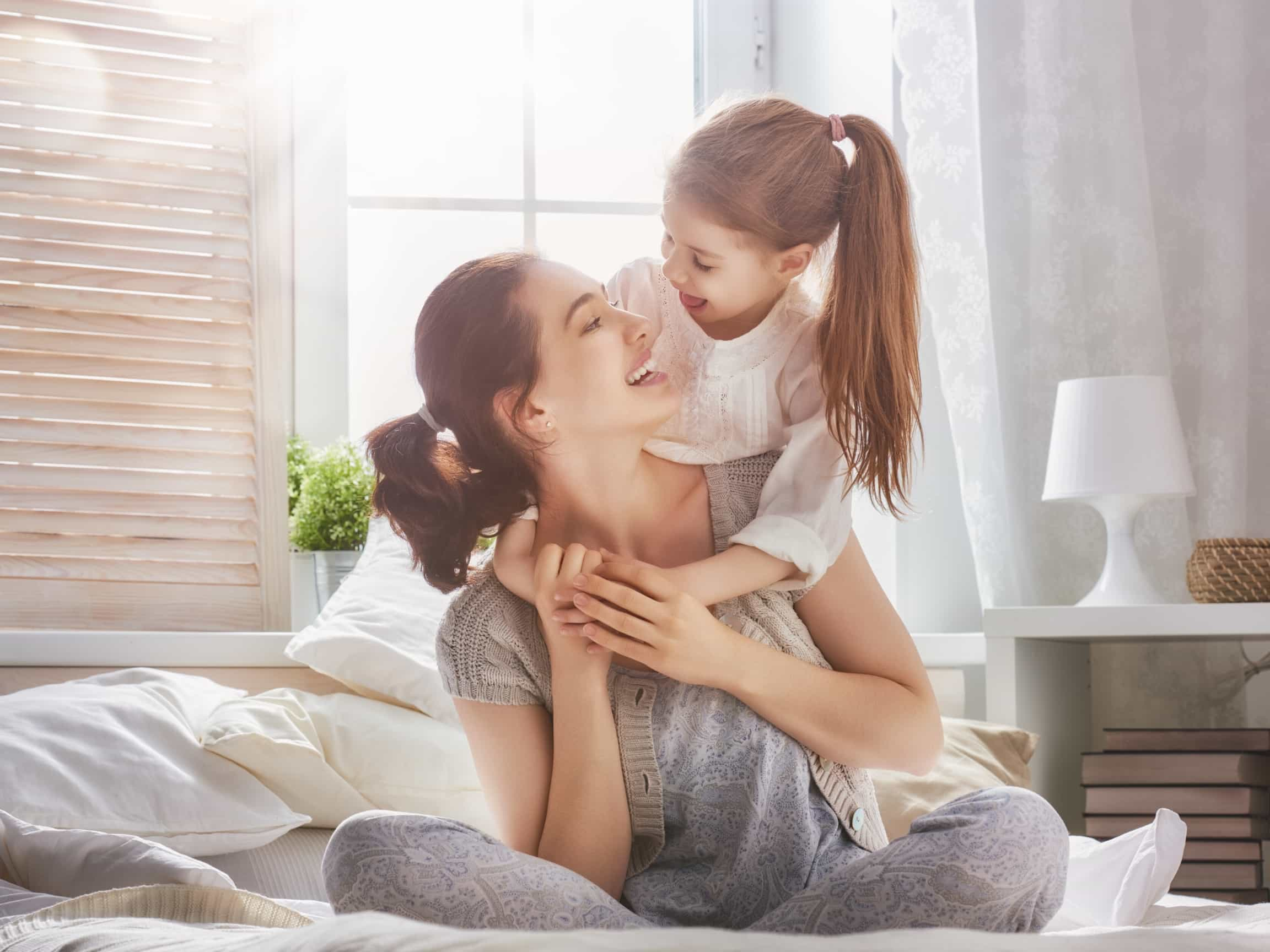 A mother and her daughter sit on a bed