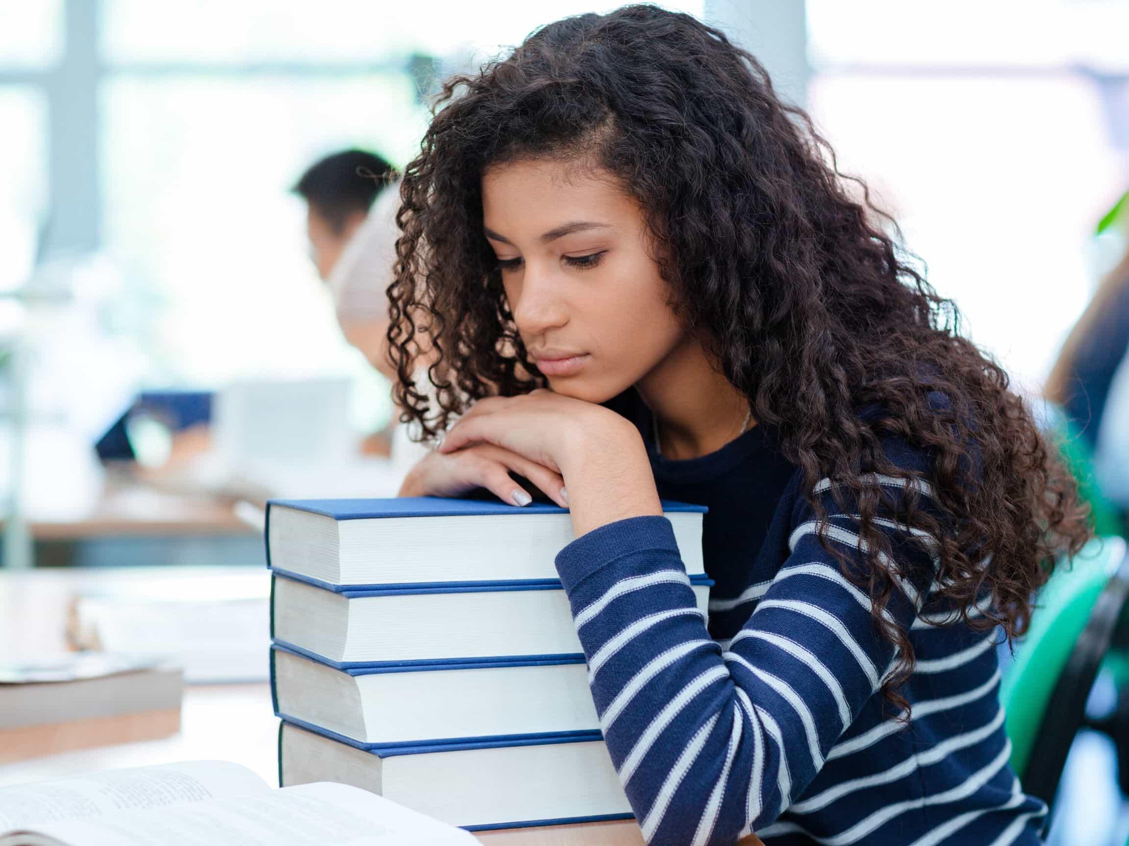 A female college student slumps over a pile of books