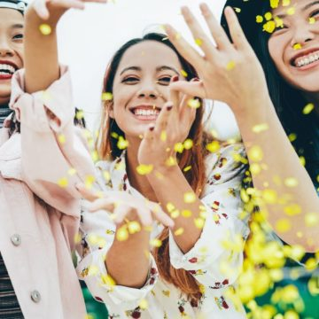Group of female friends smiling while tossing flower petals in the air