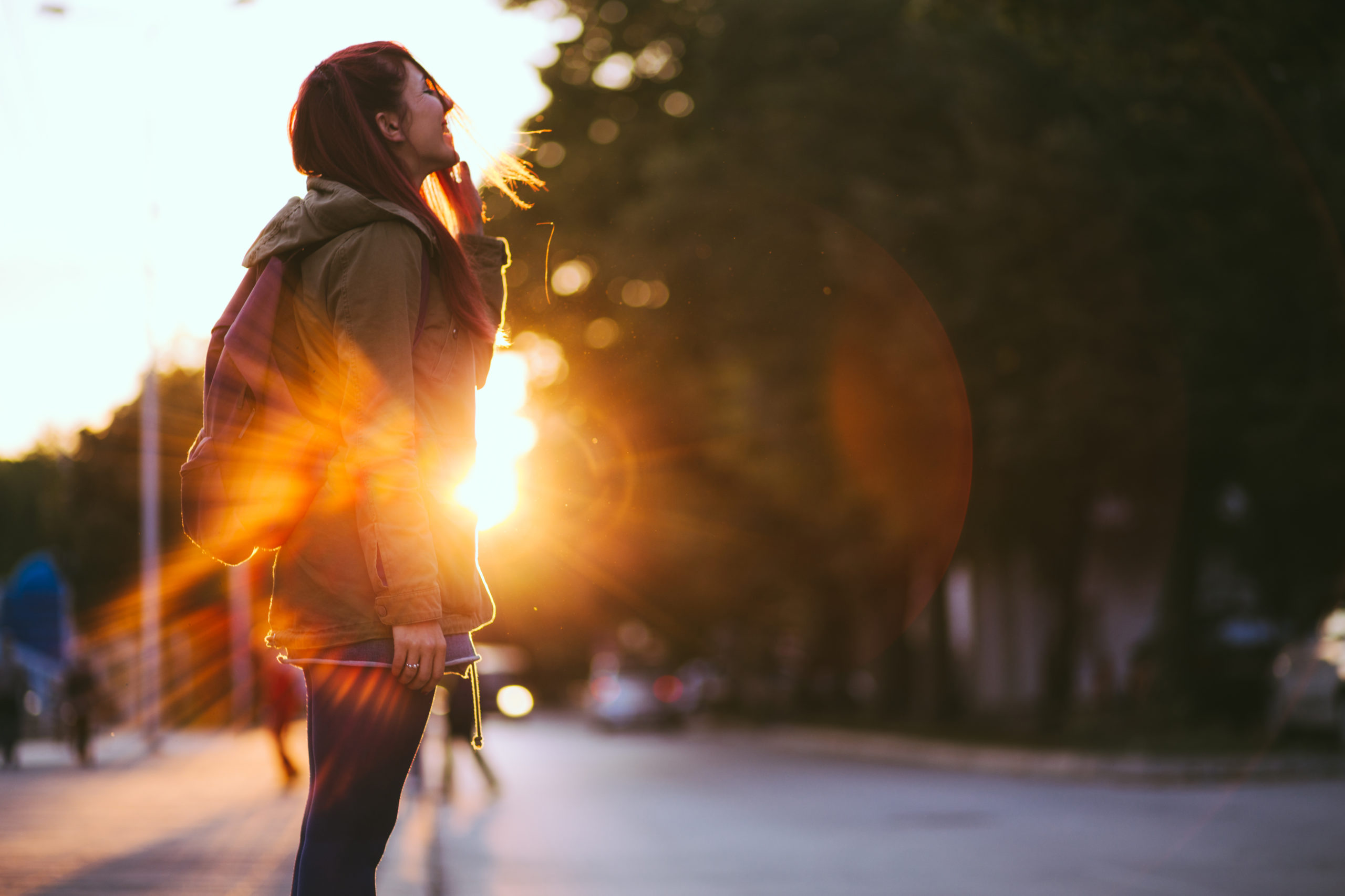 Smiling Young Red-haired woman dressed in jacket is enjoying vivid sunset in the streets.